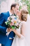 拿着婚礼花束的亲吻的新婚佳偶的侧视图 免版税图库摄影