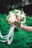 拿着婚礼花束的新娘由玫瑰做成 免版税库存照片