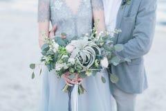 拿着婚礼花束的新婚的夫妇 图库摄影