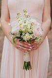 拿着婚礼花束的桃红色礼服的新娘 免版税库存照片
