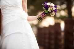 拿着婚礼花束的熟悉内情的新娘 库存图片