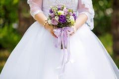 拿着婚礼花束的白色礼服的新娘 婚姻概念 库存图片