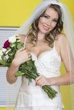 拿着婚礼花束花的可爱的年轻新娘 免版税库存图片