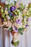拿着婚礼花束,新娘花束的白色礼服的年轻美丽的新娘从玫瑰色奶油色浪花,玫瑰丛,玫瑰紫色Memor的 库存图片