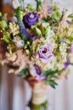 拿着婚礼花束,新娘花束的白色礼服的年轻美丽的新娘从玫瑰色紫色回忆,紫罗兰色南北美洲香草的,eucal 免版税库存照片