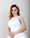拿着婚礼花束,明亮的异常的出现的婚礼礼服的红发新娘 美好的婚礼发型和 库存图片