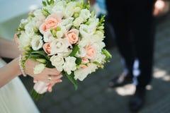 拿着婚礼花花束的新娘户外 免版税库存照片
