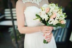 拿着婚礼花花束的新娘户外 图库摄影