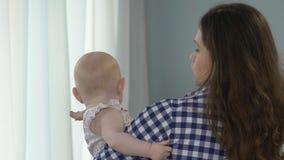 拿着婴儿,孩子的女性支持的窗口看起来被混淆的转过来 股票视频