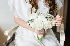 拿着嫩花束的一套白色婚礼礼服的新娘 新娘闺房 库存照片