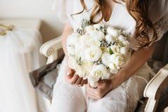 拿着嫩花束的一套白色婚礼礼服的新娘 新娘闺房 免版税库存照片
