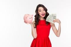 拿着存钱罐和金钱的可爱的愉快的年轻卷曲妇女 免版税图库摄影