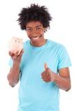 拿着存钱罐和minking拇指的年轻黑人少年人 免版税图库摄影
