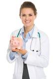 拿着存钱罐的微笑的医生妇女 库存照片