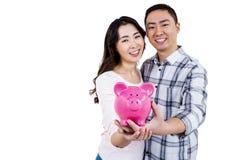 拿着存钱罐的快乐的夫妇画象  免版税图库摄影