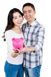 拿着存钱罐的愉快的微笑的夫妇画象  库存图片