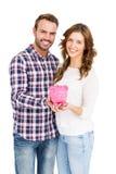 拿着存钱罐的愉快的年轻夫妇 图库摄影