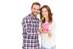 拿着存钱罐的愉快的年轻夫妇 免版税库存照片