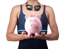拿着存钱罐的游泳者 免版税库存图片
