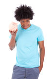 拿着存钱罐-非洲人民的年轻黑人少年人 免版税库存照片