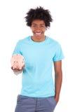 拿着存钱罐-非洲人民的年轻黑人少年人 库存照片