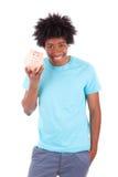 拿着存钱罐-非洲人民的年轻黑人少年人 免版税图库摄影