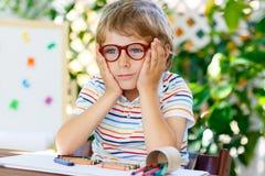 戴拿着学校设备的眼镜的小孩男孩 免版税库存图片