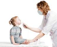 拿着孩子呼吸的医生吸入器面具 免版税库存图片