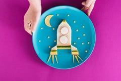 拿着孩子的人滑稽的五颜六色的早餐火箭形状的有月亮和星的在蓝色板材 免版税库存图片