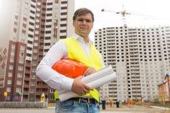拿着安全帽和图纸的微笑的男性工程师画象  免版税库存照片