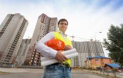 拿着安全帽的安全背心的年轻建筑工程师 库存照片