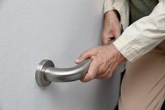 拿着安全步行的年长妇女扶手栏杆 免版税库存照片