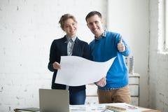 拿着完成的建筑图纸的同事 免版税库存照片