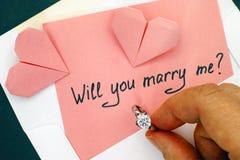 拿着定婚戒指的人手 与文本的信件将您m 库存照片