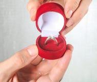 拿着定婚戒指的人的手被隔绝在白色 库存图片