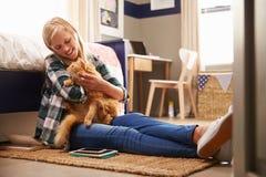 拿着宠物猫的女孩在她的卧室 免版税库存图片