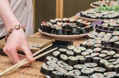 拿着寿司的少妇的胳膊 免版税库存图片