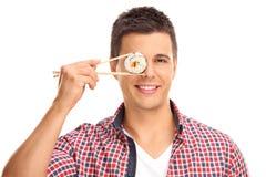 拿着寿司的片断在他的眼睛前面的人 库存图片