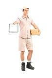 拿着小包和给signatu的送报员一张剪贴板 免版税库存照片