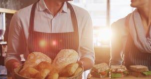 拿着小圆面包和三明治的侍者和女服务员 股票录像