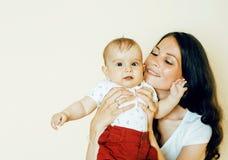拿着小孩小儿子,乳房费的年轻深色的愉快的母亲 免版税库存照片