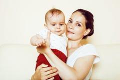 拿着小孩小儿子,乳房费的年轻深色的愉快的母亲 免版税库存图片