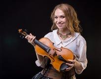 拿着小提琴的微笑的女孩 库存照片