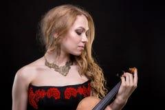 拿着小提琴的年轻白肤金发的女孩 库存照片