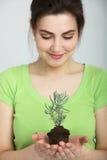 拿着小植物的微笑的俏丽的妇女 库存图片