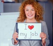 拿着小海报的红发微笑的女实业家 免版税图库摄影