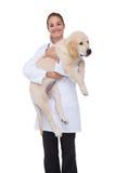 拿着小狗的微笑的狩医 免版税库存图片