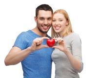 拿着小红色心脏的微笑的夫妇 免版税库存照片