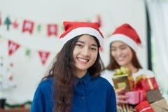 拿着小组有smili的当前箱子的xmas党的亚洲妇女 库存照片