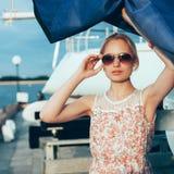 拿着小船的花礼服和太阳镜的白肤金发的女孩航行 免版税库存照片
